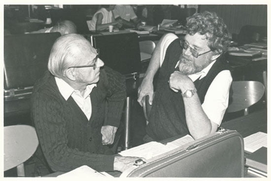 Photograph of Dr. Harvey Conn, seated at right, speaking with an